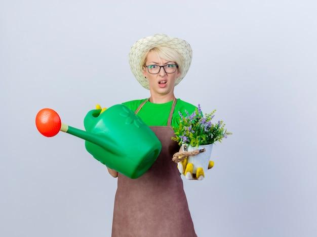 Jovem jardineira com cabelo curto no avental e chapéu segurando um regador e um vaso de planta ficando confusa e descontente