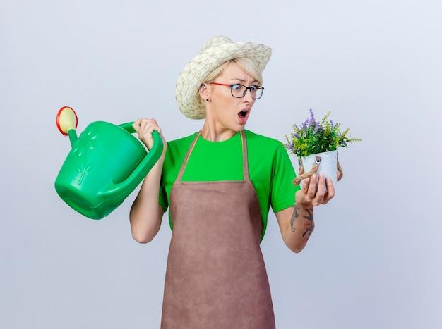 Jovem jardineira com cabelo curto no avental e chapéu segurando um regador e um vaso de planta olhando para uma planta sendo surpreendida