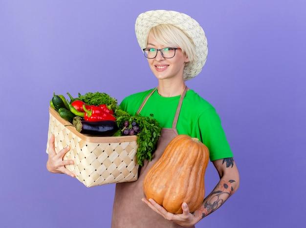 Jovem jardineira com cabelo curto no avental e chapéu segurando uma caixa cheia de legumes e um lookign de abóbora para a câmera sorrindo alegremente em pé sobre um fundo azul