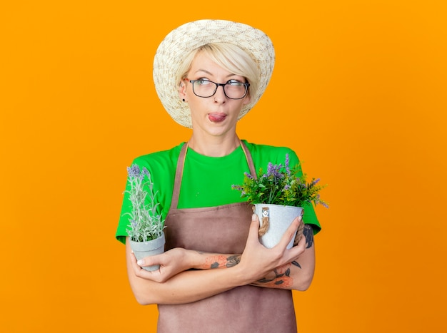 Jovem jardineira com cabelo curto no avental e chapéu segurando vasos de plantas lookign ao lado mostrando a língua em pé sobre um fundo laranja