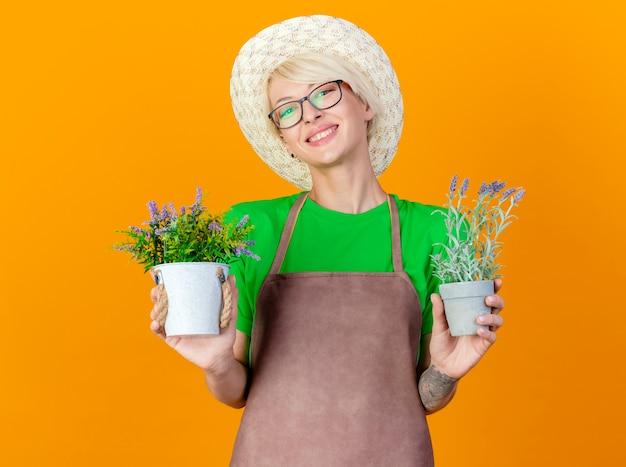 Jovem jardineira com cabelo curto no avental e chapéu segurando vasos de plantas lookign para a câmera sorrindo alegremente em pé sobre um fundo laranja