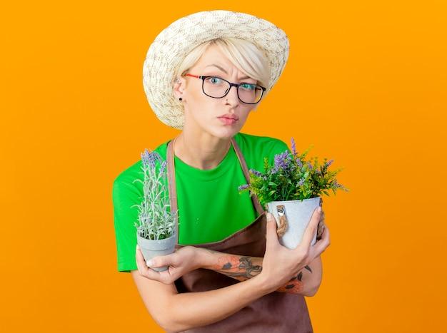Jovem jardineira com cabelo curto no avental e chapéu segurando vasos de plantas olhando para a câmera confusa em pé sobre um fundo laranja