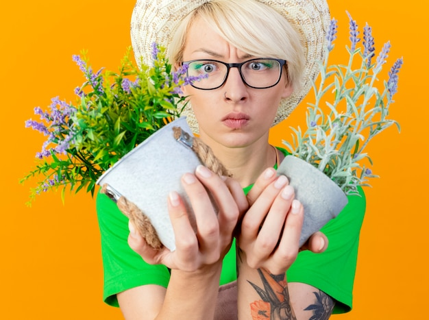 Jovem jardineira com cabelo curto no avental e chapéu segurando vasos de plantas olhando para eles ficando descontente em pé sobre um fundo laranja
