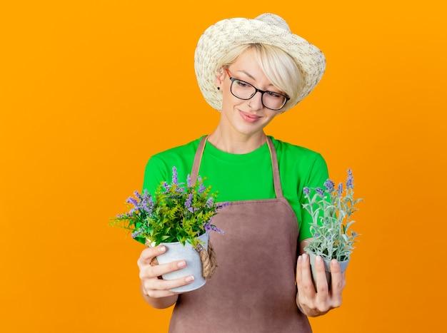 Jovem jardineira com cabelo curto no avental e chapéu segurando vasos de plantas olhando para eles sorrindo com uma cara feliz em pé sobre um fundo laranja