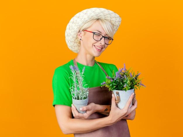 Jovem jardineira com cabelo curto no avental e chapéu segurando vasos de plantas sorrindo alegremente feliz e positiva em pé sobre um fundo laranja