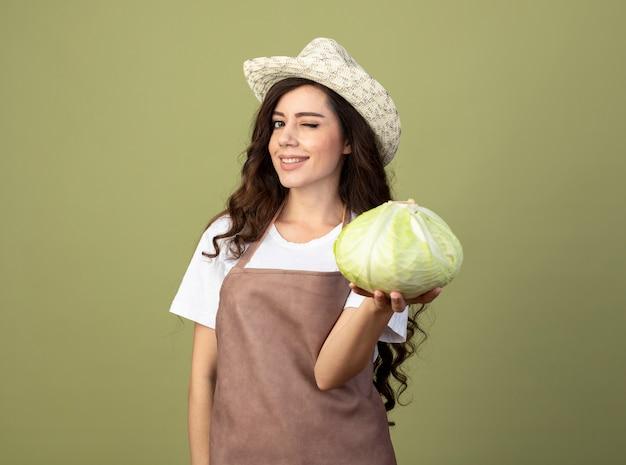 Jovem jardineira confiante em uniforme, usando chapéu de jardinagem, pisca os olhos e segura o repolho isolado na parede verde oliva