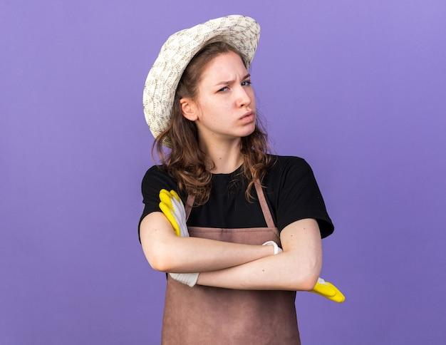 Jovem jardineira confiante usando chapéu de jardinagem e luvas cruzando as mãos
