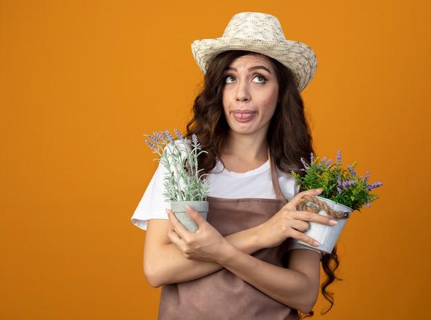 Jovem jardineira confusa de uniforme usando chapéu de jardinagem enfia a língua e segura vasos de flores olhando para cima, isolados na parede laranja com espaço de cópia