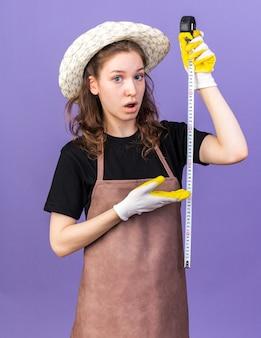 Jovem jardineira confusa usando chapéu de jardinagem com luvas de alongamento e aponta para a fita métrica