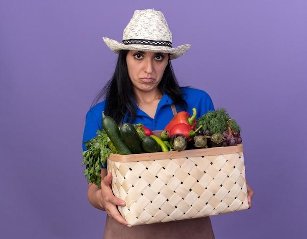 Jovem jardineira confusa vestindo uniforme e chapéu segurando uma cesta de legumes, olhando para a frente, isolada na parede roxa com espaço de cópia