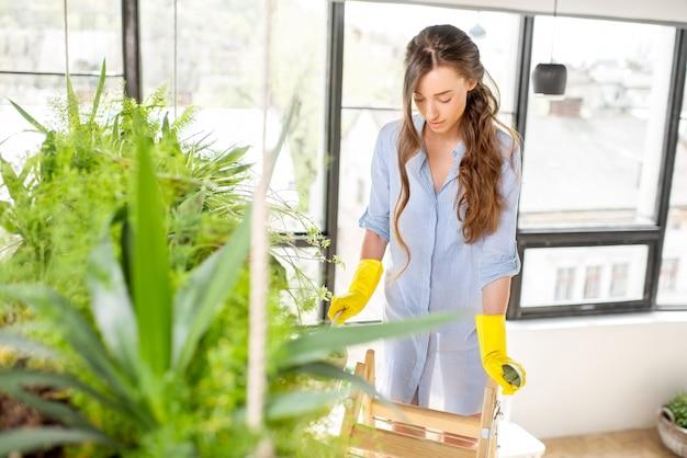 Jovem jardineira cuidando das plantas na escada do laranjal