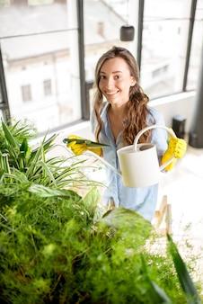 Jovem jardineira cuidando de plantas em pé com um regador na escada do laranjal