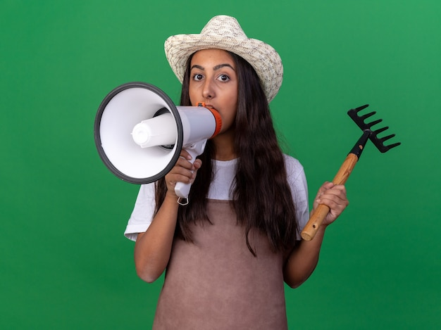 Jovem jardineira de avental e chapéu de verão segurando um mini ancinho gritando para o megafone em pé sobre a parede verde