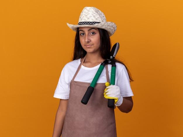Jovem jardineira de avental e chapéu de verão segurando uma tesoura de cerca viva com cara séria em pé sobre uma parede laranja