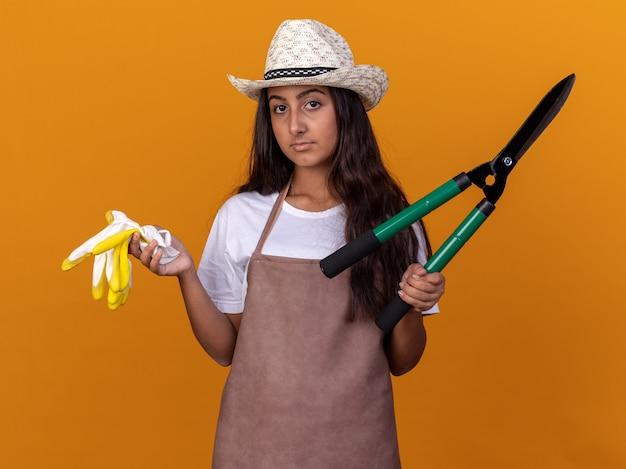 Jovem jardineira de avental e chapéu de verão segurando uma tesoura de sebe e luvas de trabalho com um sorriso no rosto em pé sobre uma parede laranja