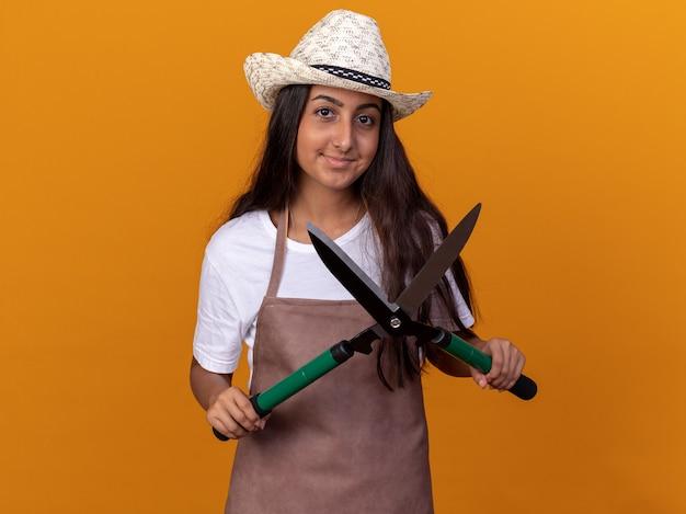 Jovem jardineira de avental e chapéu de verão segurando uma tesoura de sebes com um sorriso no rosto em pé sobre uma parede laranja