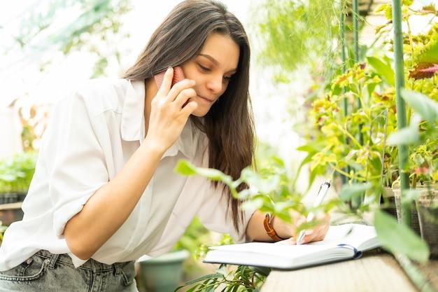 Jovem jardineira de mulheres de negócios falando ao telefone, escrevendo no caderno em estufa