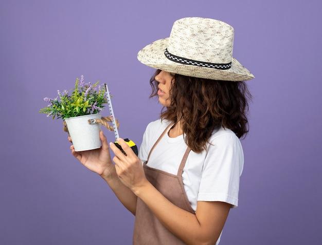 Jovem jardineira de uniforme vestindo um chapéu de jardinagem medindo uma flor em um vaso de flores com fita métrica