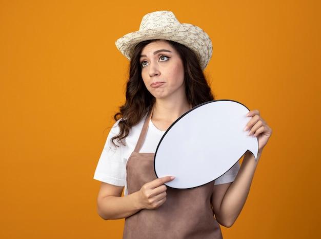 Jovem jardineira desapontada de uniforme, usando chapéu de jardinagem, segurando um balão de fala olhando para o lado isolado na parede laranja