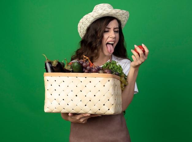 Jovem jardineira descontente em uniforme com chapéu de jardinagem enfia a língua para fora segurando uma cesta de vegetais e tomate isolado na parede verde