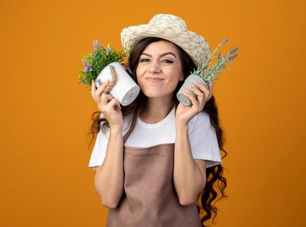 Jovem jardineira empolgada de uniforme, usando chapéu de jardinagem, segurando vasos de flores isolados na parede laranja com espaço de cópia
