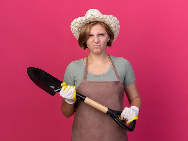 Jovem jardineira eslava, irritada, usando luvas e chapéu de jardinagem, segurando uma pá isolada na parede rosa com espaço de cópia
