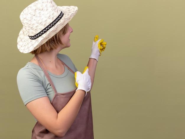 Jovem jardineira eslava sorridente usando luvas e chapéu de jardinagem olhando e apontando para trás