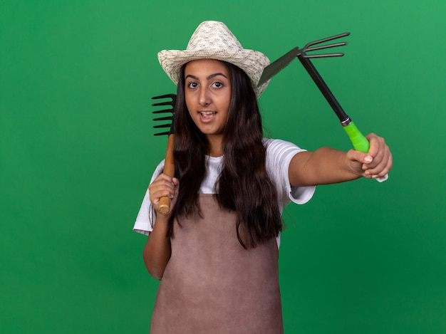 Jovem jardineira feliz com avental e chapéu de verão segurando um mini ancinho e enxadinha com um sorriso no rosto em pé sobre a parede verde