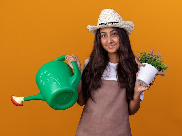 Jovem jardineira feliz com avental e chapéu de verão segurando um regador e um vaso de planta com um sorriso no rosto em pé sobre uma parede laranja