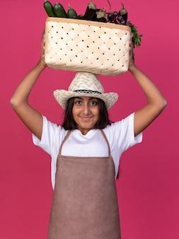 Jovem jardineira feliz com avental e chapéu de verão segurando uma caixa cheia de legumes na cabeça com um sorriso no rosto em pé sobre a parede rosa
