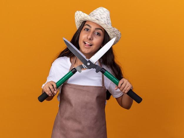 Jovem jardineira feliz com avental e chapéu de verão segurando uma tesoura de cerca-viva e sorrindo alegremente em pé sobre a parede laranja