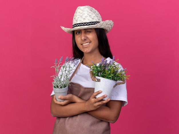 Jovem jardineira feliz com avental e chapéu de verão segurando vasos de plantas sorrindo e piscando em pé sobre a parede rosa