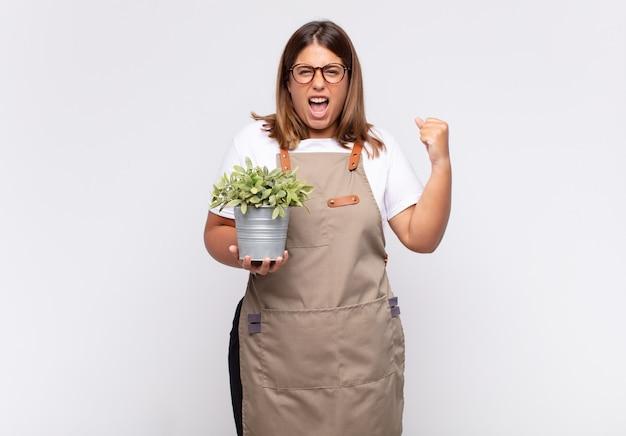 Jovem jardineira gritando agressivamente com uma expressão de raiva ou com os punhos cerrados celebrando o sucesso