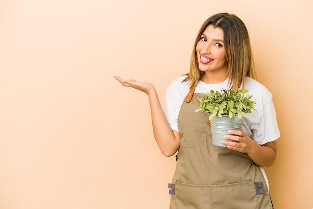 Jovem jardineira indiana segurando uma planta isolada mostrando um espaço de cópia na palma da mão e segurando a outra mão na cintura