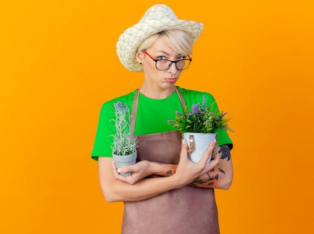 Jovem jardineira insatisfeita com cabelo curto, avental e chapéu segurando vasos de plantas olhando para a câmera, carrancuda em pé sobre um fundo laranja