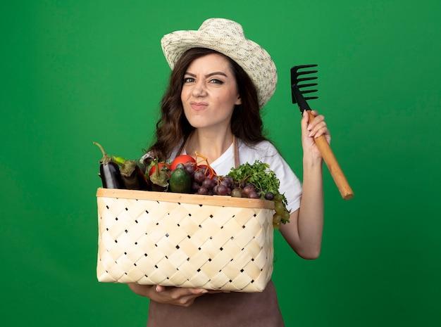 Jovem jardineira insatisfeita de uniforme, usando chapéu de jardinagem, segurando uma cesta de vegetais e um ancinho isolado na parede verde