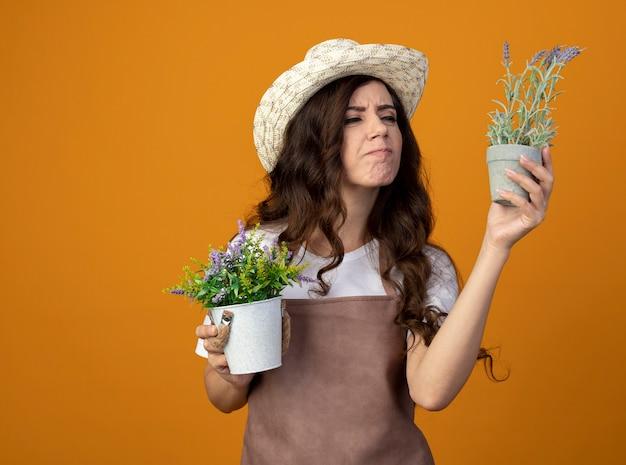 Jovem jardineira insatisfeita de uniforme, usando chapéu de jardinagem, segurando vasos de flores isolados na parede laranja com espaço de cópia