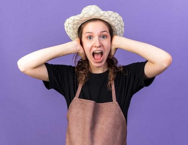 Jovem jardineira irritada com chapéu de jardinagem, orelhas cobertas com as mãos isoladas na parede azul