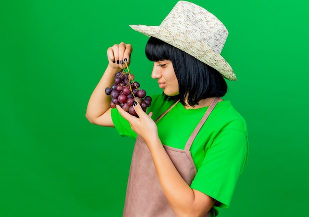 Jovem jardineira irritada de uniforme, usando chapéu de jardinagem, segurando e olhando para as uvas