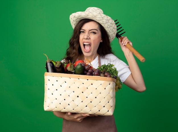 Jovem jardineira irritada de uniforme, usando chapéu de jardinagem, segurando uma cesta de vegetais e um ancinho isolados na parede verde