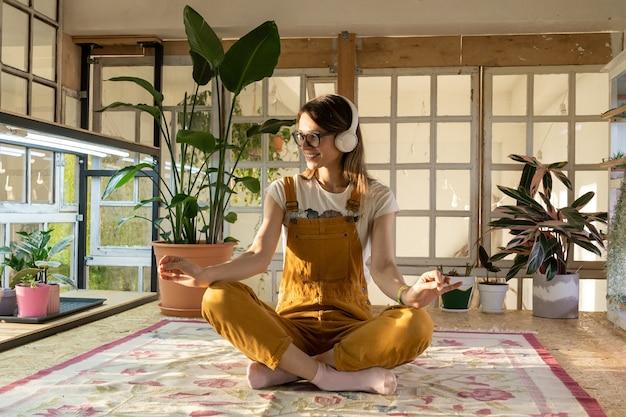 Jovem jardineira meditando com macacão e fones de ouvido relaxantes do estudo ou do trabalho
