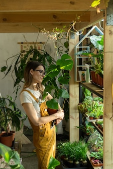 Jovem jardineira ou florista segurando vaso de flores com mostera trabalhando no jardim doméstico ou estufa