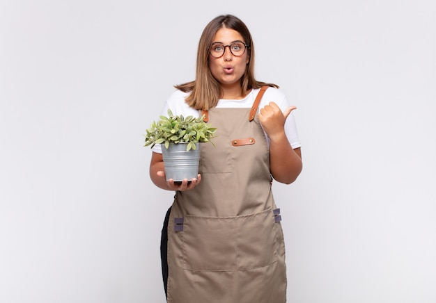 Jovem jardineira parecendo espantada e incrédula, apontando para um objeto ao lado e dizendo uau, inacreditável