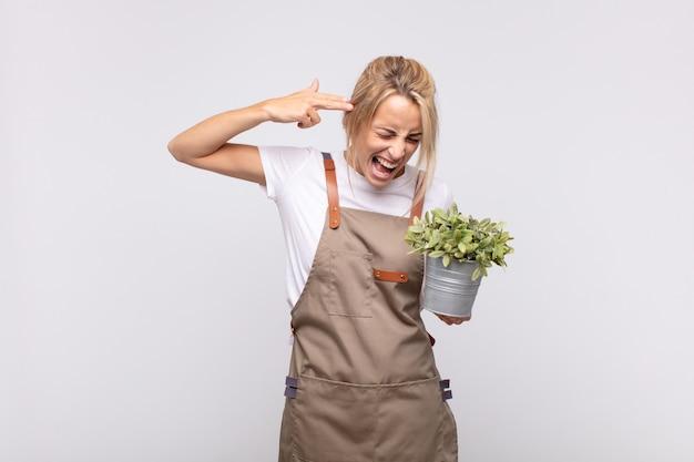 Jovem jardineira parecendo infeliz e estressada, gesto suicida fazendo sinal de arma com a mão, apontando para a cabeça