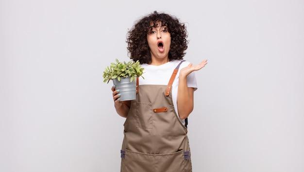 Jovem jardineira parecendo surpresa e chocada, com o queixo caído segurando um objeto com a mão aberta na lateral