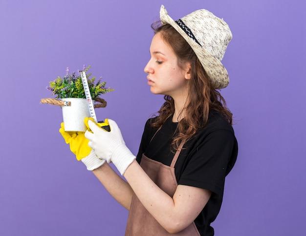 Jovem jardineira pensando, usando chapéu de jardinagem com luvas, medindo flores em um vaso de flores com fita métrica isolada na parede azul