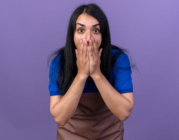 Jovem jardineira preocupada, usando uniforme, com as mãos na boca, olhando para a frente, isolada na parede roxa