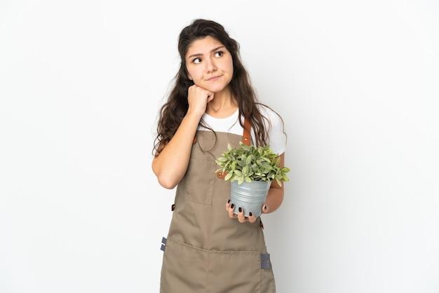Jovem jardineira russa segurando uma planta isolada, tendo dúvidas e pensando
