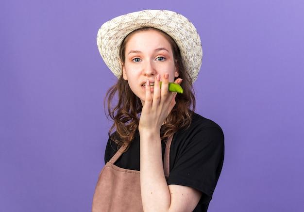 Jovem jardineira satisfeita com um chapéu de jardinagem segurando pimenta e mostrando gesto de fumar isolado na parede azul