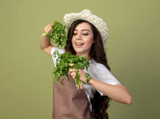 Jovem jardineira satisfeita em uniforme com um chapéu de jardinagem segura e olha para o coentro isolado na parede verde oliva